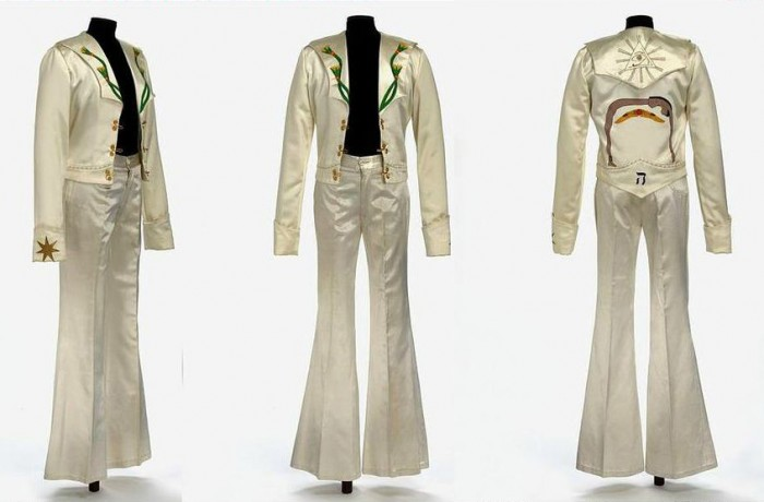 Jimmy Page Stage Outfit 1975. Currently displayed at the V&A Museum, London: Painted satin and gold cord. By Malcolm Hall. This stage costume, worn by Jimmy Page, of Led Zeppelin, is known as  the 'Egyptian' costume because of the symbols prominent on the back of the satin jacket. These symbols are more than just decoration, however, reflecting Page's interest in the occult, and particularly the teachings of early 20th Century British occultist and writer Aleister Crowley. As well as having meaning in the symbols, the ivory satin costume itself would have been highly eye-catching, reflecting Page's wild performance style.